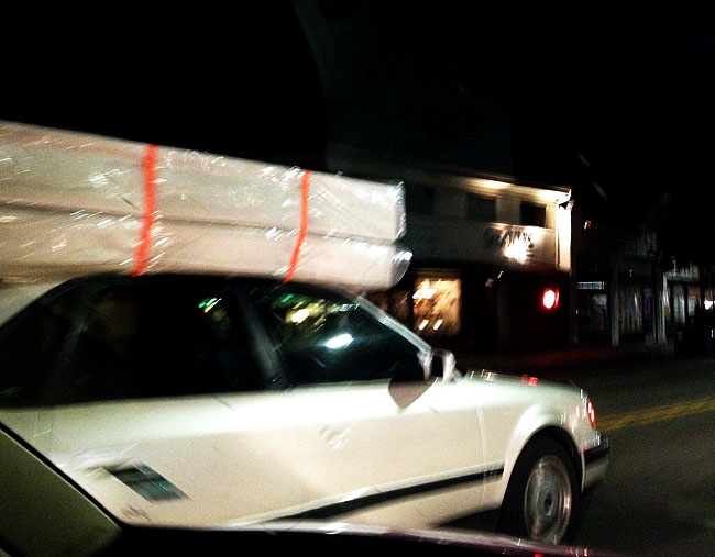 How do you transport a bed? Apparently you can just strap it to the roof of your friend's car!